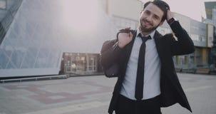 Immeuble de bureaux moderne un homme d'affaires dans un sourire de costume charismatique devant l'appareil-photo banque de vidéos