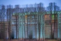 Immeuble trouble de réflexion avec des arbres dans l'eau Photos libres de droits