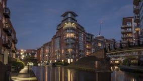 Immeubles modernes, allumés au crépuscule, donnant sur une voie d'eau urbaine Photographie stock