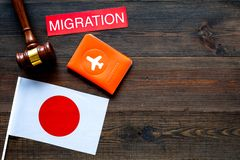 Immigration to Japan concept. Text immigration near passport cover and japanese flag, hammer on dark wooden background stock image