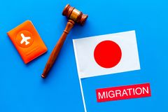 Immigration to Japan concept. Text immigration near passport cover and japanese flag, hammer on blue background top view royalty free stock image