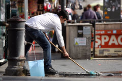 A immigrant cleans the road. Just outside the metro station Spagna in Rome (Italy stock images