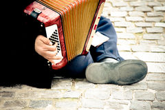 Immigrant playing accordion. Poor immigrant playing an accordion on the street stock photography