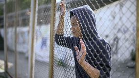Immigrant teenager behind fence dreaming about bright future and safety, refugee. Stock photo royalty free stock image