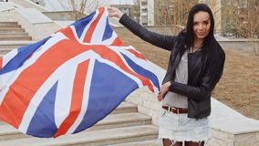 Immigranten patriottische activisten Latino meisje die met de golvende vlag van Groot-Brittannië in handen camera en het glimlach stock videobeelden