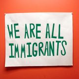 Immigrants and immigration sign with political undertones stock photography