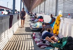 Immigrants at US Mexico border. Asylum seekers  waiting on the Progreso International Bridge between Us and Mexico. The Bridge  connects the cities of Progreso stock photo
