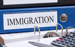 Immigration binder on desk in the office. Immigration - blue binder with text on desk in the office with pen and calculator Stock Photo