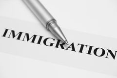 Immigration. Concept. Ballpoint pen and word . Focus on the end of ballpoint pen. Shallow depth of field. Black and White. Close-up stock image