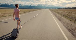 Immigration concept. Downshifting. Alone woman with suitcase walk on empty road to wild nature stock footage