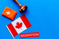 Immigration to Canada concept. Text immigration near passport cover and canadian flag, hammer on blue background top. Immigration concept. Text immigration near stock photo