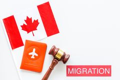 Immigration to Canada concept. Text immigration near passport cover and canadian flag, hammer on white background top. Immigration concept. Text immigration near royalty free stock images