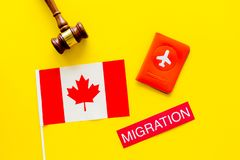 Immigration to Canada concept. Text immigration near passport cover and canadian flag, hammer on yellow background top. Immigration concept. Text immigration royalty free stock images