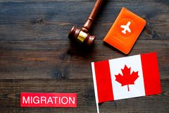 Immigration to Canada concept. Text immigration near passport cover and canadian flag, hammer on dark wooden background. Immigration concept. Text immigration royalty free stock images