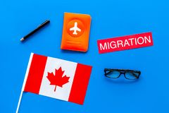 Immigration to Canada concept. Text immigration near passport cover and canadian flag on blue background top view stock photo