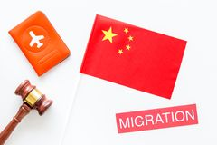 Immigration to China concept. Text innigration near passport cover and chinese flag, judge hammer on white background. Immigration concept. Text visa near stock image