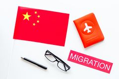 Immigration to China concept. Text innigration near passport cover and chinese flag on white background top view. Immigration concept. Text visa near passport stock image