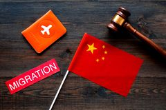 Immigration to China concept. Text innigration near passport cover and chinese flag, judge hammer on dark wooden. Immigration concept. Text visa near passport royalty free stock photo