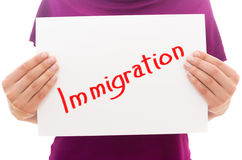 Immigration. Girl holding white paper sheet with text Immigration royalty free stock images