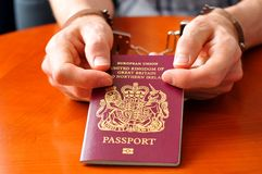 Immigration. Illegal immigration concept with hands holding UK passport Stock Image