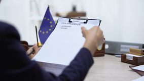 Immigration inspector denying visa application, European Union flag on table. Stock footage stock video