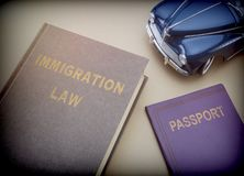 Immigration law book next to a passport and blue miniature vehicle. Conceptual image stock images