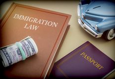 Immigration law book next to a passport and blue miniature vehicle. Conceptual image royalty free stock images