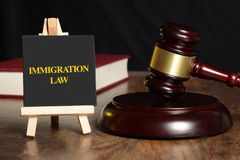 Immigration Law with gavel and book in background.  stock image