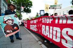 Immigration March: Stop the Raids. WASHINGTON, DC - MAY 1, 2009: On International Workers' Day, immigrants and their supporters, some carrying signs designed by Stock Photo