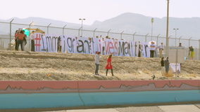 Immigration Rally on the Border. People gather near the border fence for a pro-immigration rally stock video footage