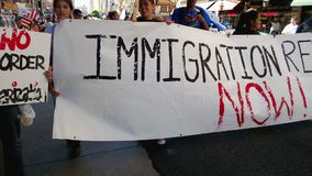 Immigration Reform Banner. A large white picket banner that reads, Immigration Reform Now! is held up and carried by multiple people during an immigration rally