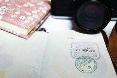 Immigration stamp on a passport. Blurred background of camera and notebook. Travelling concept. Royalty Free Stock Images