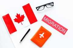 Immigration to Canada concept. Text immigration near passport cover and canadianflag on white background top view.  royalty free stock images