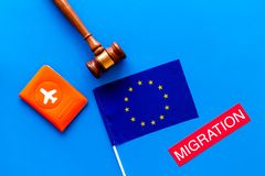 Schengen visa. Immigration to Europe concept. Text immigration near passport cover and european flag on blue background. Immigration to Europe concept. Text stock photo