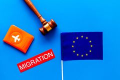 Schengen visa. Immigration to Europe concept. Text immigration near passport cover and european flag on blue background. Immigration to Europe concept. Text royalty free stock image