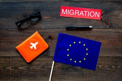 Schengen visa. Immigration to Europe concept. Text immigration near passport cover and european flag on dark wooden. Immigration to Europe concept. Text stock images