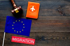 Schengen visa. Immigration to Europe concept. Text immigration near passport cover and european flag, hammer on dark. Immigration to Europe concept. Text stock photo