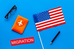Immigration to United States of America concept. Textimmigration near passport cover and USA flag on blue background top. View stock photos