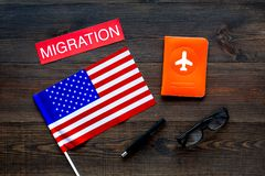 Immigration to United States of America concept. Textimmigration near passport cover and USA flag on dark wooden. Background top view royalty free stock images
