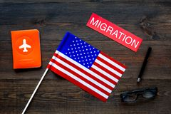 Immigration to United States of America concept. Textimmigration near passport cover and USA flag on dark wooden. Background top view royalty free stock photography