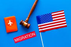 Immigration to United States of America concept. Textimmigration near passport cover and USA flag, judge hammer on blue. Background top view stock image