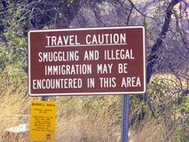 Immigration Travel Caution Sign in Arizona. An Travel Caution Sign in Arizona near the Mexico border warns of smuggling and illegal immigration royalty free stock photography