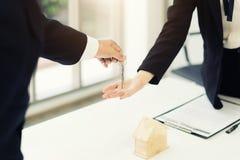 Immobilienagentur, die dem Wohnungsinhaber Schlüssel, kaufenden Verkauf gibt lizenzfreies stockfoto