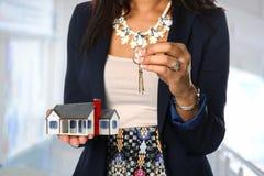 Immobilienagentur, die Haus und Schlüssel hält stockfoto