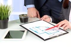 Immobilienagentur, die Hauspläne zu einem businesssman zeigt Fokus auf einem Stift und einer Hand Lizenzfreie Stockfotos