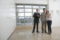 Immobilienagentur-Showing Couple New-Wohnung lizenzfreies stockbild