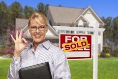Immobilienagentur vor Verkaufszeichen und Haus Stockbilder