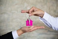 Immobilienagenturholding-Hausschl?ssel zu seinem Kunden, nachdem Vertragsvereinbarung im B?ro, das Konzept f?r Immobilien unterze stockbilder
