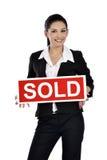 Immobilienfrau, die ein Verkaufszeichen hält Stockfoto