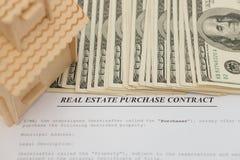 Immobilienkontakt und ein Architekturmodell und ein Stapel USD-Währung Stockbild